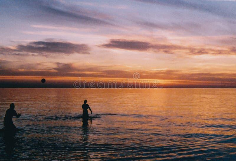 Gente que juega con una bola en la playa en el agua fotografía de archivo