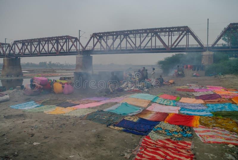Gente que lava y que seca el paño en los bancos arenosos del río de Yamuna, Agra, la India fotografía de archivo
