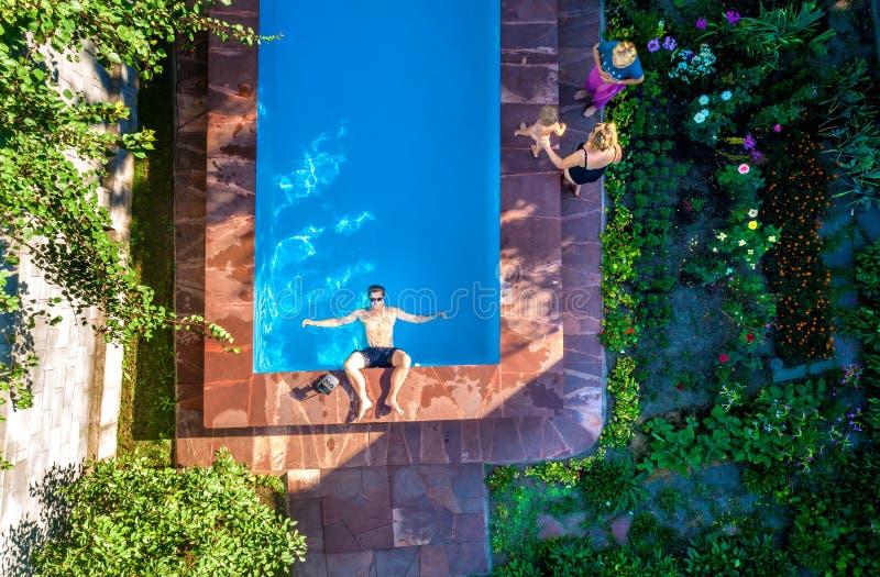 Gente que miente en los ociosos del sol cerca de la piscina, visión superior foto de archivo