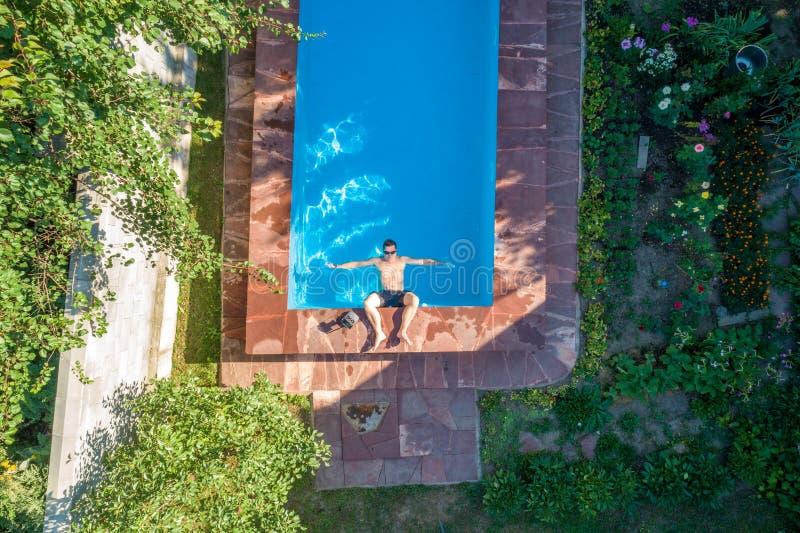 Gente que miente en los ociosos del sol cerca de la piscina, visión superior fotos de archivo