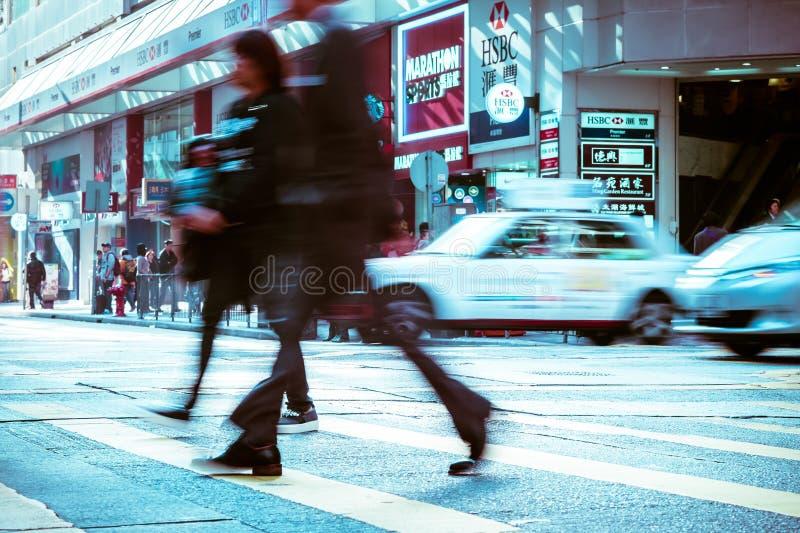 Gente que mueve encendido el paso de peatones de la cebra en la ciudad apretada Hon Kong imágenes de archivo libres de regalías