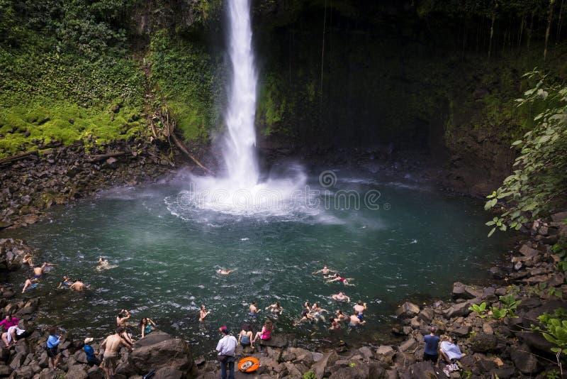 Gente que nada en la piscina de la cascada de Fortuna del La en Costa Rica imagenes de archivo