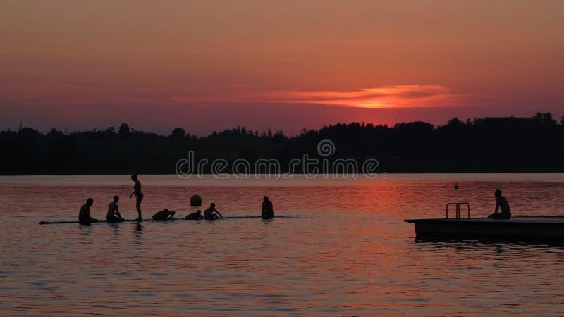 Gente que nada en la puesta del sol fotos de archivo libres de regalías