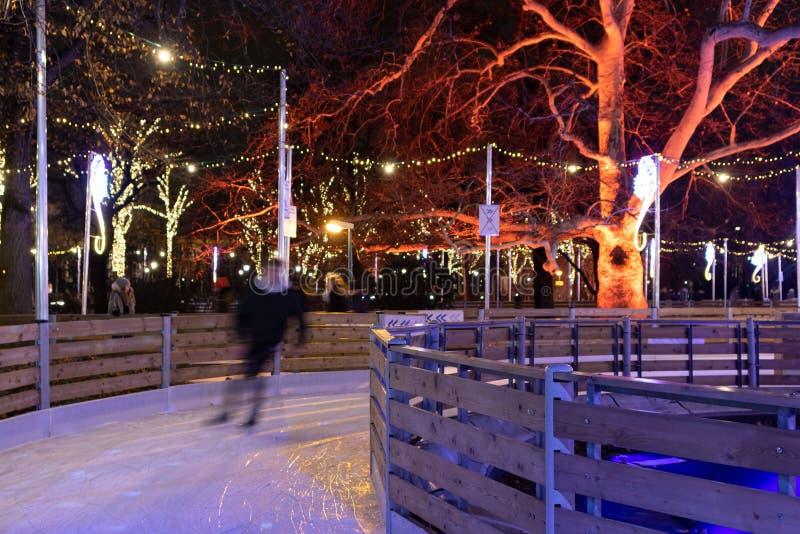 Gente que patina sobre hielo en la pista de hielo cerca de la ciudad Hall Rathaus al lado del mercado famoso de la Navidad en Vie imágenes de archivo libres de regalías