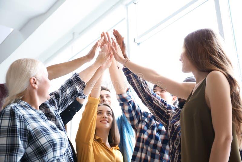 Gente que pone las manos juntas dentro Concepto de la unidad foto de archivo