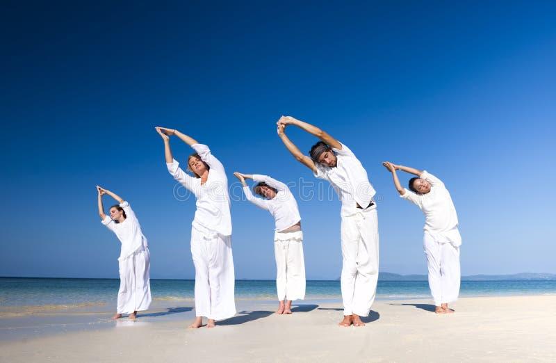 Gente que realiza concepto del paisaje de la playa de la yoga foto de archivo libre de regalías