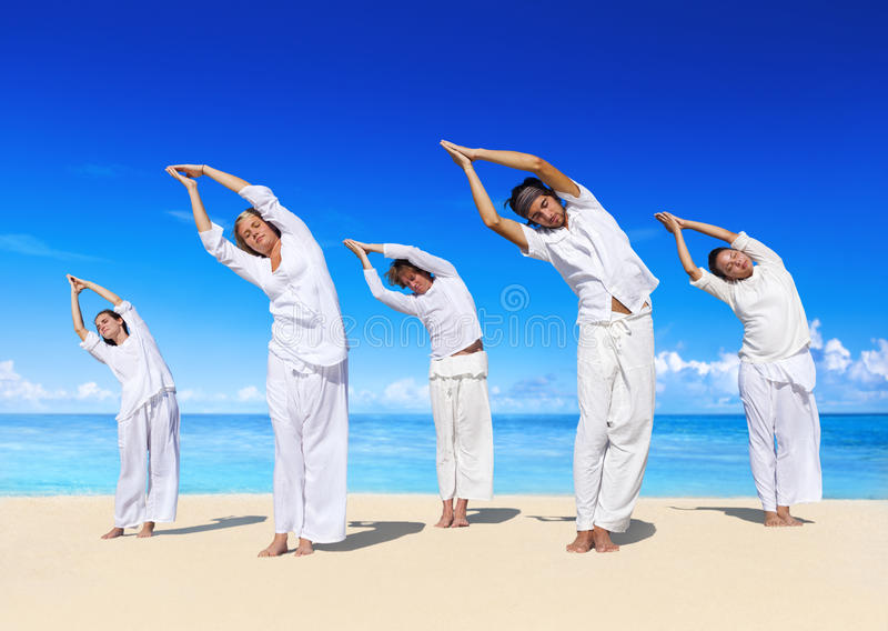 Gente que realiza yoga en la playa fotos de archivo