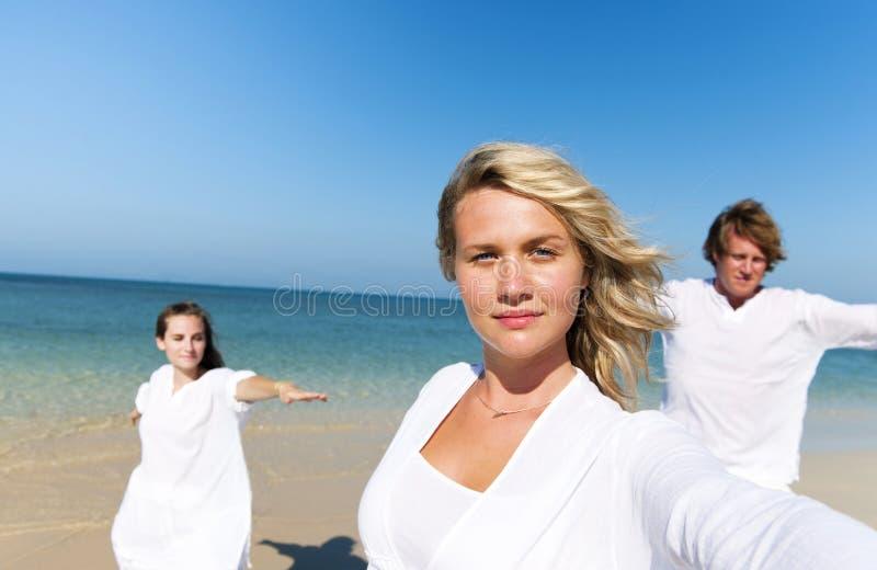Gente que realiza yoga en la playa imagen de archivo