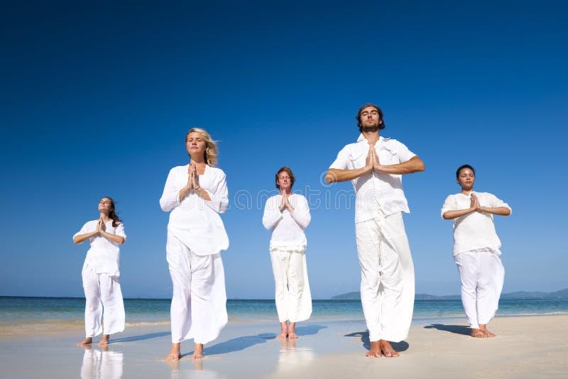Gente que realiza yoga en la playa fotos de archivo libres de regalías