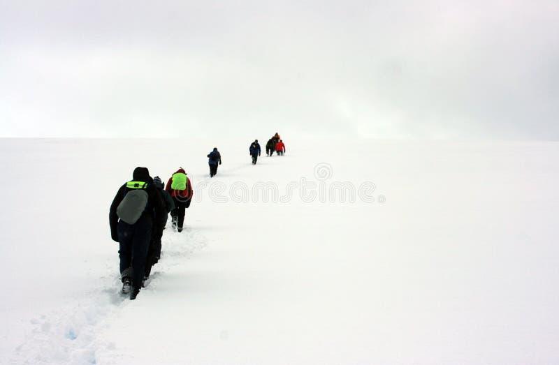 Gente que recorre al horizonte de la nieve foto de archivo