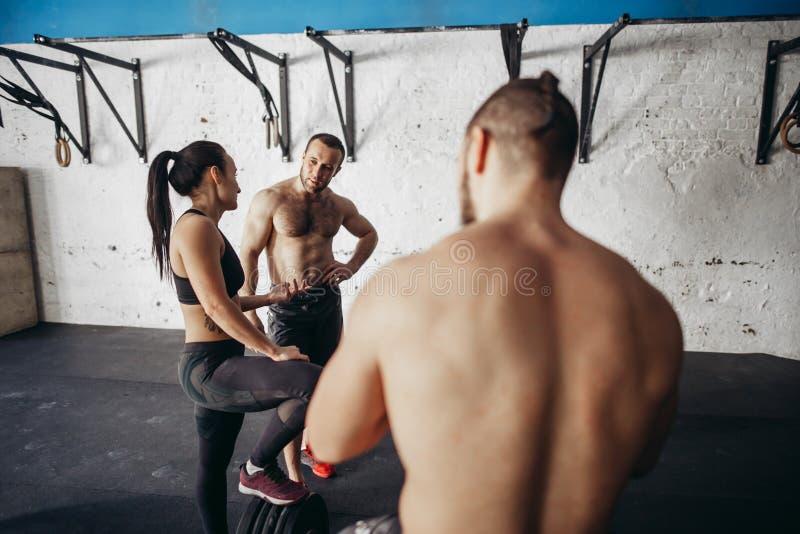Gente que relaja y que toma una rotura después de resolver en un gimnasio del cruz-entrenamiento imagenes de archivo