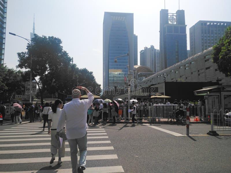 Gente que se coloca en una cola en el exterior Consulado general de Estados Unidos en Guangzhou, foto de archivo libre de regalías