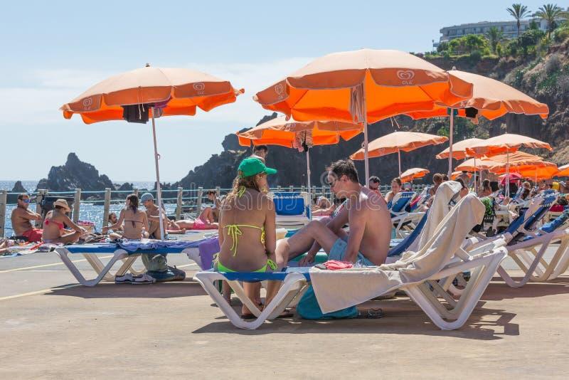 Gente que se sienta debajo de un parasol en un baño de natación público en Madeira, Portugal imagen de archivo