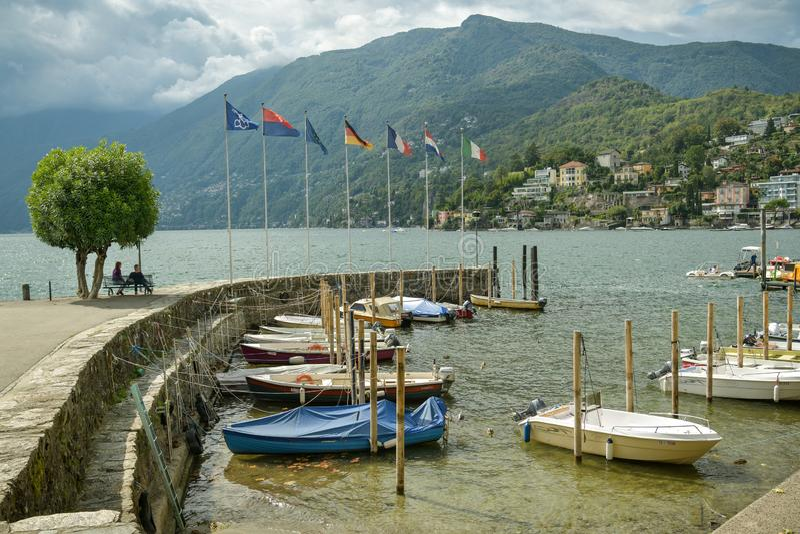 Gente que se sienta en banco cerca de pequeño puerto en Lago Maggiore en Ascona, Suiza foto de archivo