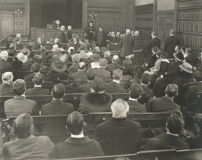 Gente que se sienta en bancos en sala de tribunal fotos de archivo