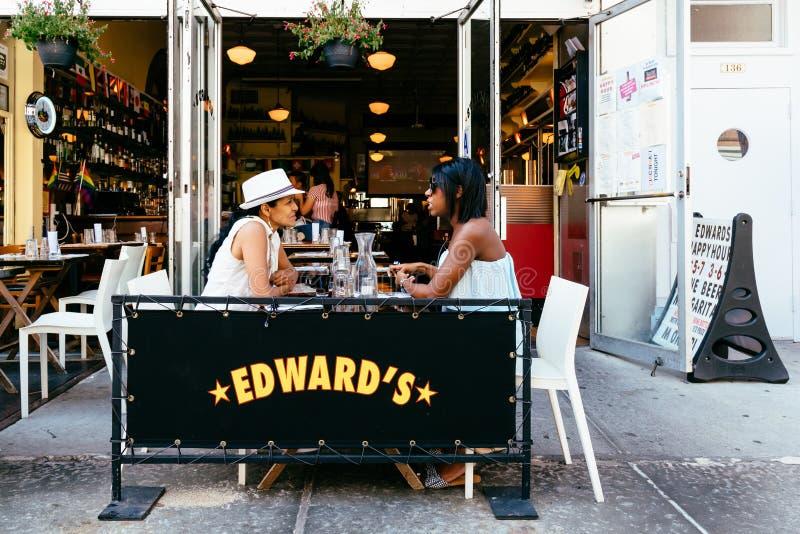 Gente que se sienta en el café tradicional de la acera en Nueva York imagenes de archivo