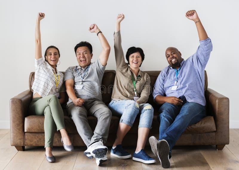 Gente que se sienta en el sofá junto fotografía de archivo libre de regalías
