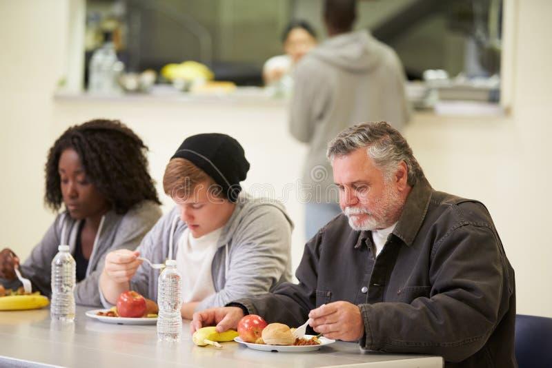 Gente que se sienta en la tabla que come la comida en refugio para personas sin techo imágenes de archivo libres de regalías