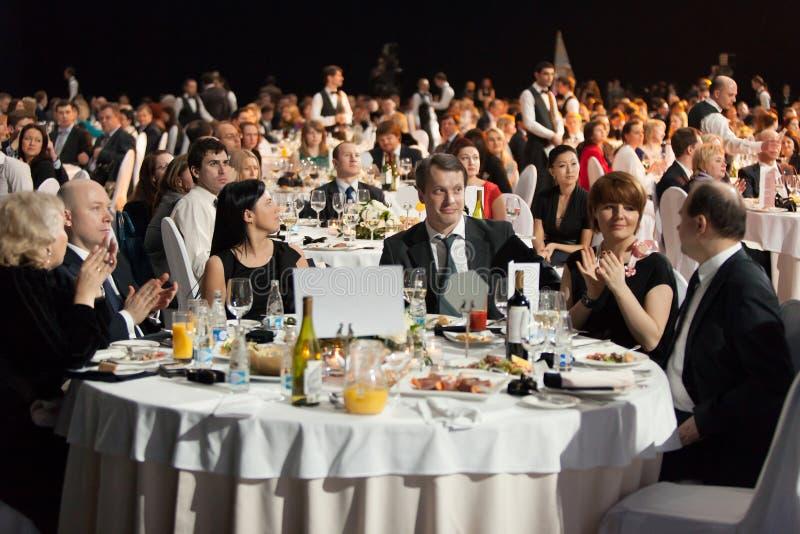 Gente que se sienta en las tablas durante la ceremonia de la recompensa imagenes de archivo