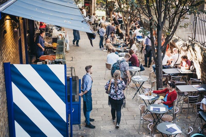 Gente que se sienta en las tablas y que camina más allá de paradas del mercado en el mercado de la ciudad, Londres, Reino Unido imagenes de archivo