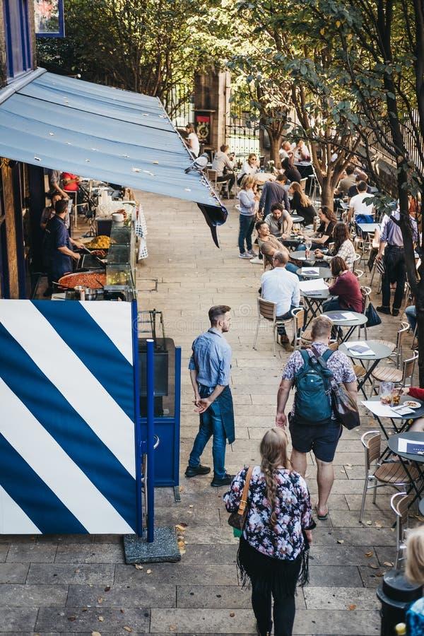 Gente que se sienta en las tablas y que camina más allá de paradas del mercado en el mercado de la ciudad, Londres, Reino Unido fotos de archivo libres de regalías