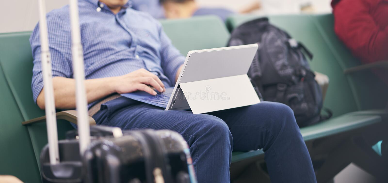Gente que se sienta y que trabaja en la tableta al esperar vuelo retrasado fotografía de archivo libre de regalías