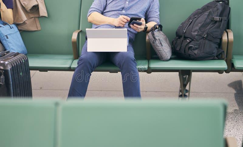 Gente que se sienta y que trabaja en la tableta al esperar vuelo retrasado fotos de archivo