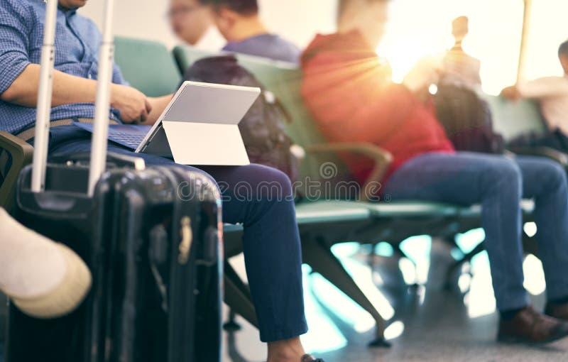 Gente que se sienta y que trabaja en la tableta al esperar vuelo retrasado imagen de archivo libre de regalías