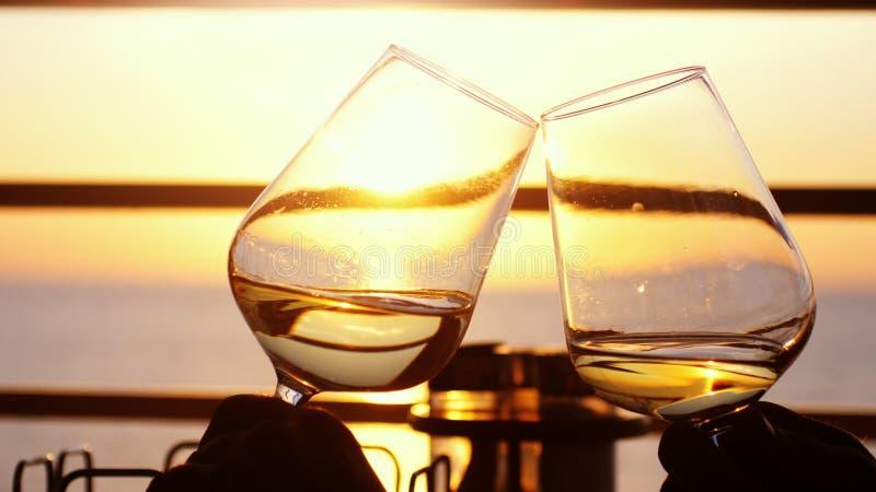 Gente que sostiene el vidrio de vino, haciendo una tostada sobre puesta del sol Amigos que beben el vino blanco, tostando tintine imagen de archivo