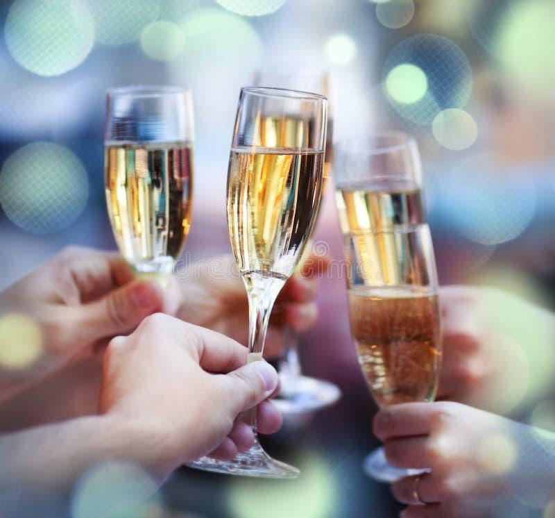 Gente que sostiene los vidrios de champán que hacen una tostada