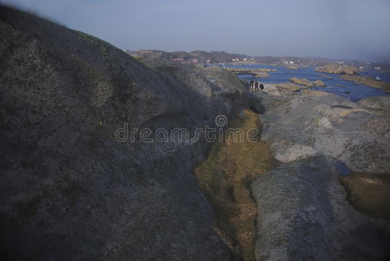 Gente que sube las rocas y el musgo en la isla imagenes de archivo