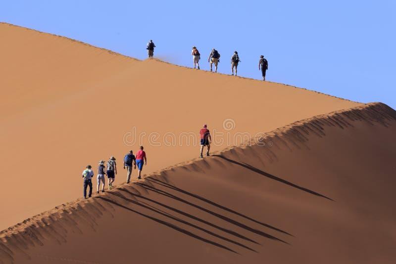 Gente que sube una duna en Sossusvlei imagenes de archivo