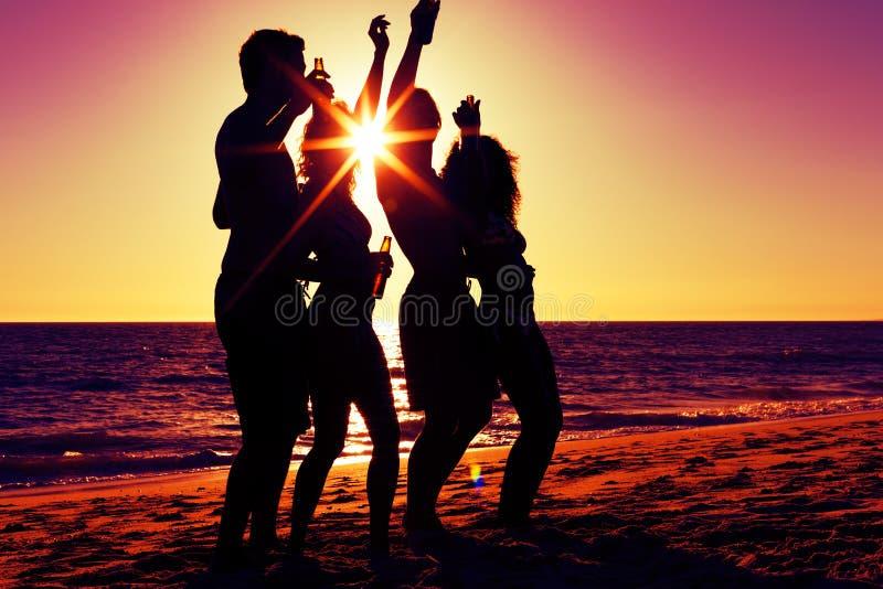 Gente que tiene partido en la playa con las bebidas imagen de archivo libre de regalías