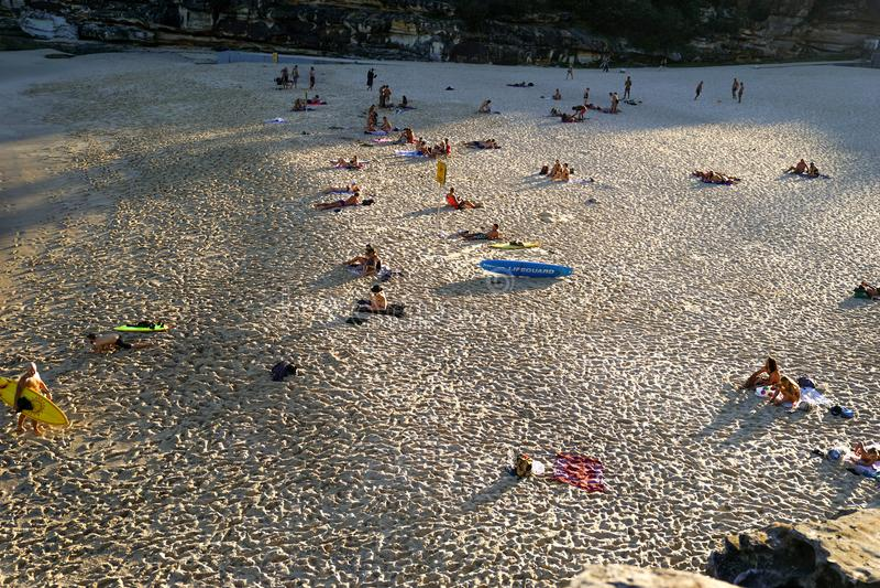 Gente que tiene sunbath en la luz del sol de la tarde en la playa de Tamarama imagen de archivo