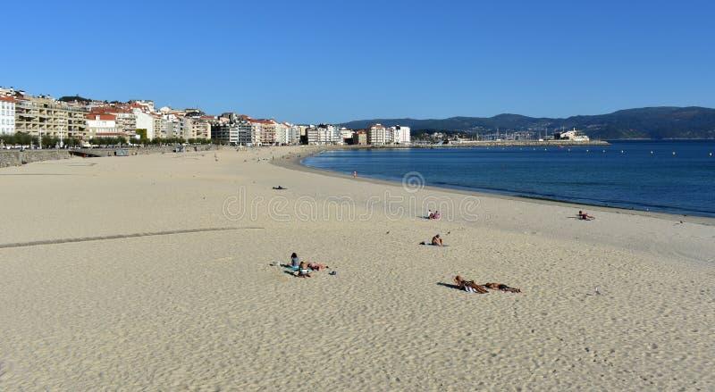 Gente que toma el sol en la playa Arena brillante y mar azul Día soleado, cielo claro Sanxenxo, Galicia, España imágenes de archivo libres de regalías