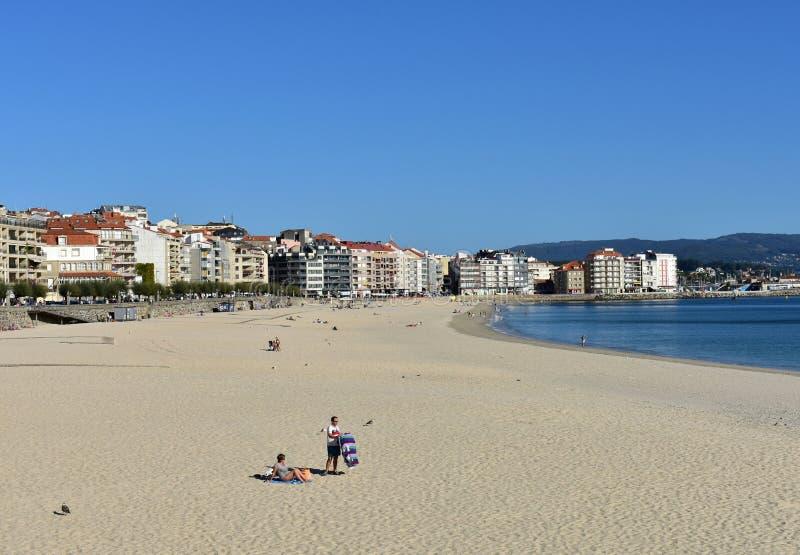 Gente que toma el sol en la playa Arena brillante y mar azul Día soleado, cielo claro Sanxenxo, Galicia, España 7 de octubre de 2 fotos de archivo libres de regalías
