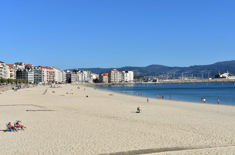 Gente que toma el sol en la playa Arena brillante y mar azul Día soleado, cielo claro Sanxenxo, Galicia, España 7 de octubre de 2 imagenes de archivo