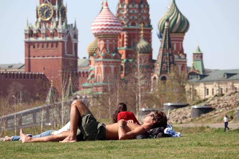 Gente que toma el sol en una hierba verde en el parque de Moscú Zaryadye fotografía de archivo