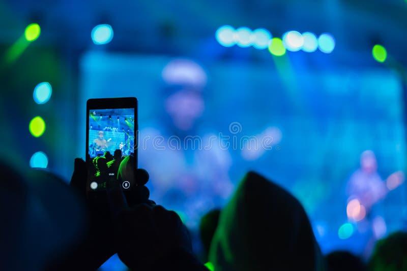 Gente que toma las fotografías con el teléfono elegante del tacto fotos de archivo