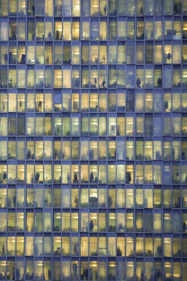 Gente que trabaja dentro de un edificio de oficinas en la noche imágenes de archivo libres de regalías