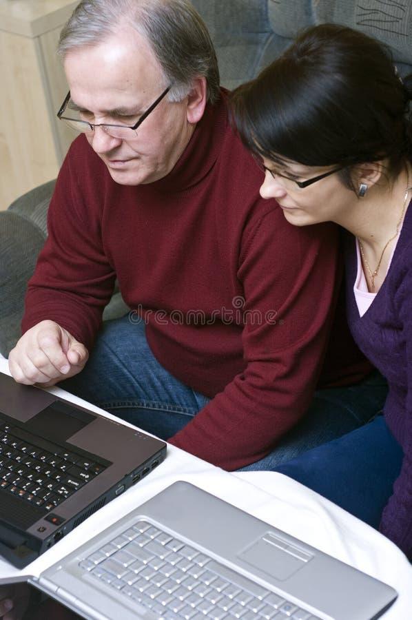 Gente que trabaja en las computadoras portátiles imagenes de archivo
