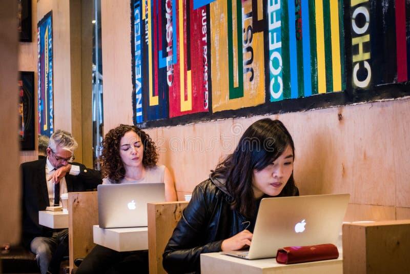 Gente que trabaja en los ordenadores en un café en el Greenwich Village, NYC fotos de archivo