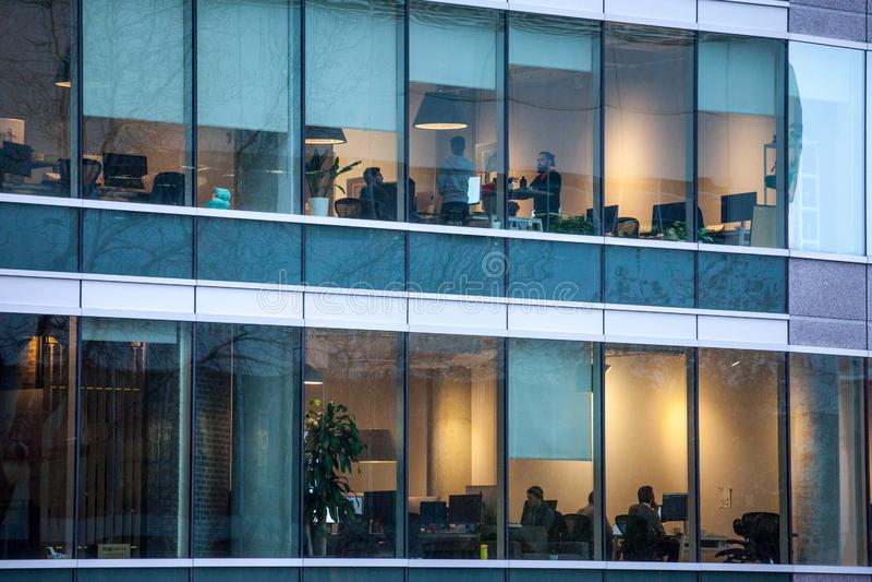 Gente que trabaja en oficinas de los espacios abiertos en un rascacielos, visto del exterior, por la tarde, en Montreal, Quebec fotos de archivo