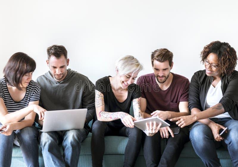 Gente que usa el dispositivo digital junto fotografía de archivo libre de regalías