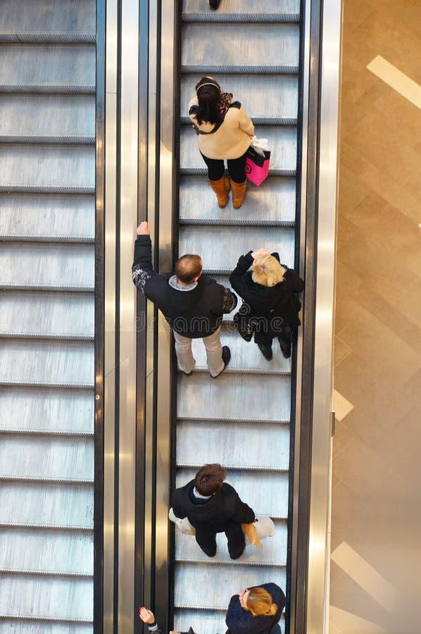 Gente que usa la escalera móvil imágenes de archivo libres de regalías