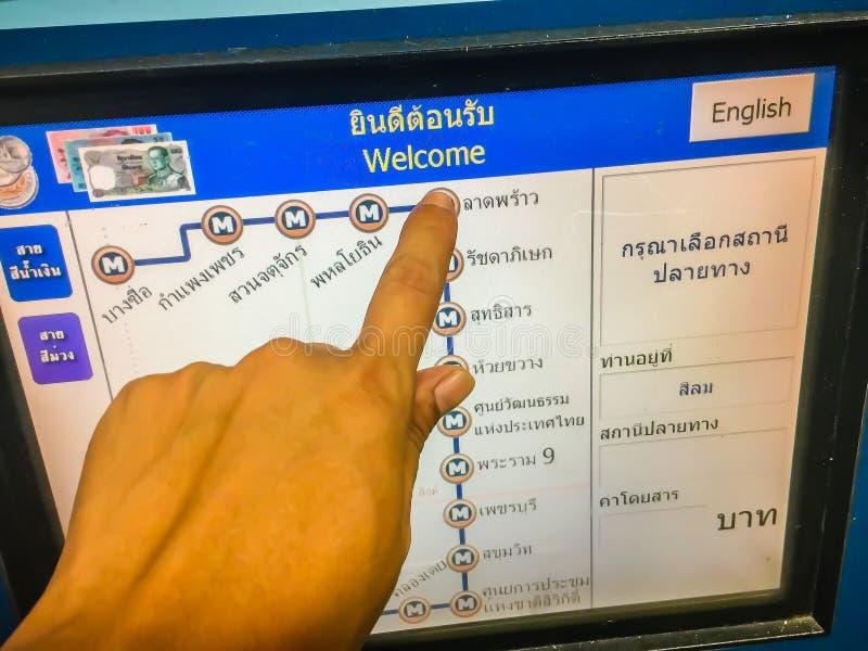 Gente que usa su finger para elegir la estación de destino durante la compra de un boleto de la moneda de MRT (tránsito rápido me foto de archivo libre de regalías