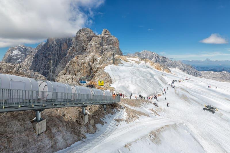Gente que va abajo en las escaleras a la superficie del glaciar de Dachstein fotos de archivo