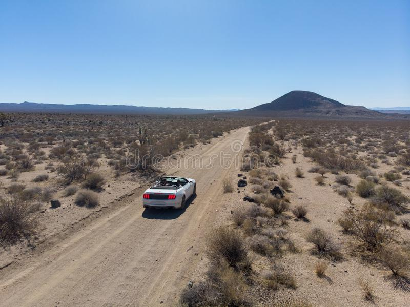 Gente que viaja en coche en el desierto y que conduce en el camino vacío escénico imagen de archivo libre de regalías