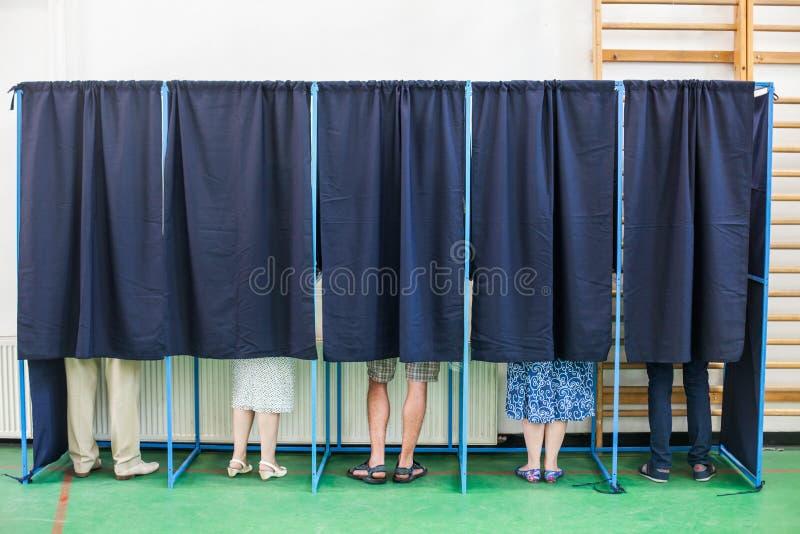 Gente que vota en cabinas imagen de archivo libre de regalías