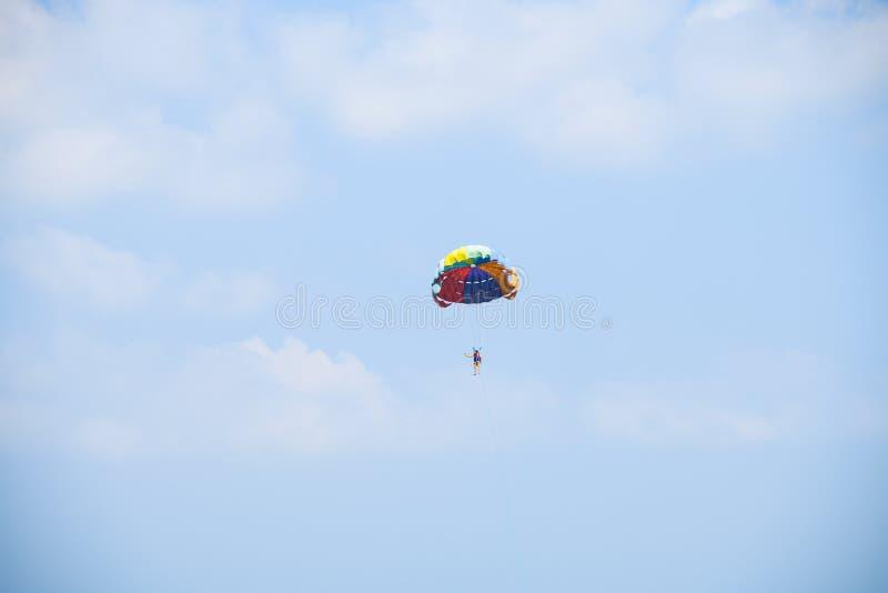 Gente que vuela en el paseo en aéreo, turismo del paracaídas de las vacaciones de verano del viaje del cielo azul del fondo imagen de archivo libre de regalías